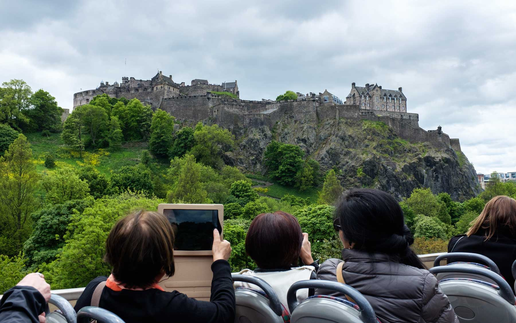 Photos of Edinburgh Castle are taken from the top of a double decker bus as it travels down Princes St.