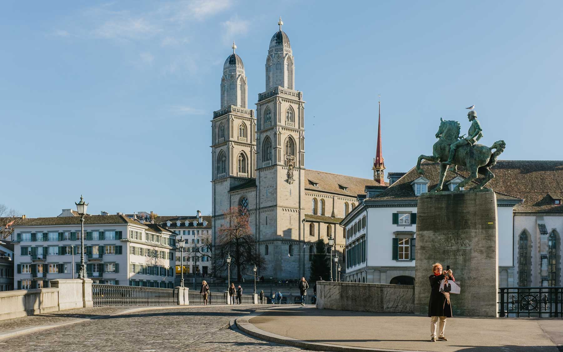 A woman frames her selfie with Zurich's Grossmünster in the background.