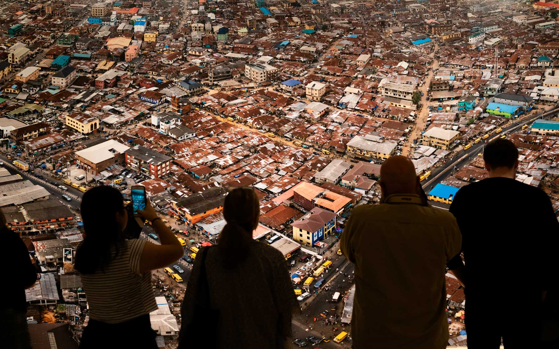 Viewers stand in front of Edward Burtynsky's aerial photo of Mushkin Market - Lagos, Nigeria.