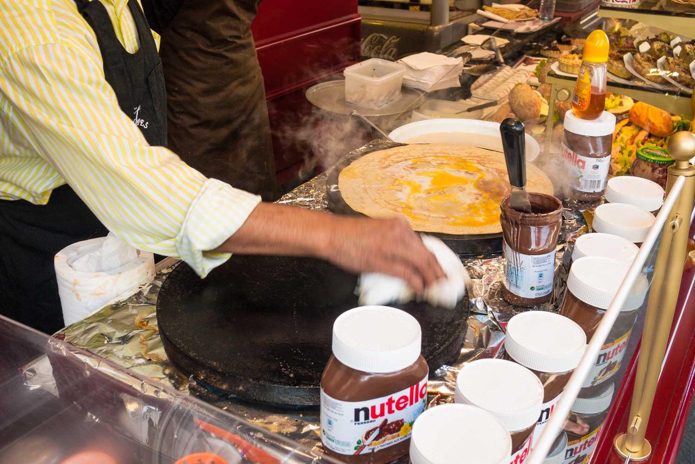 A street stall vendor prepares his equipment for a hungry customer.