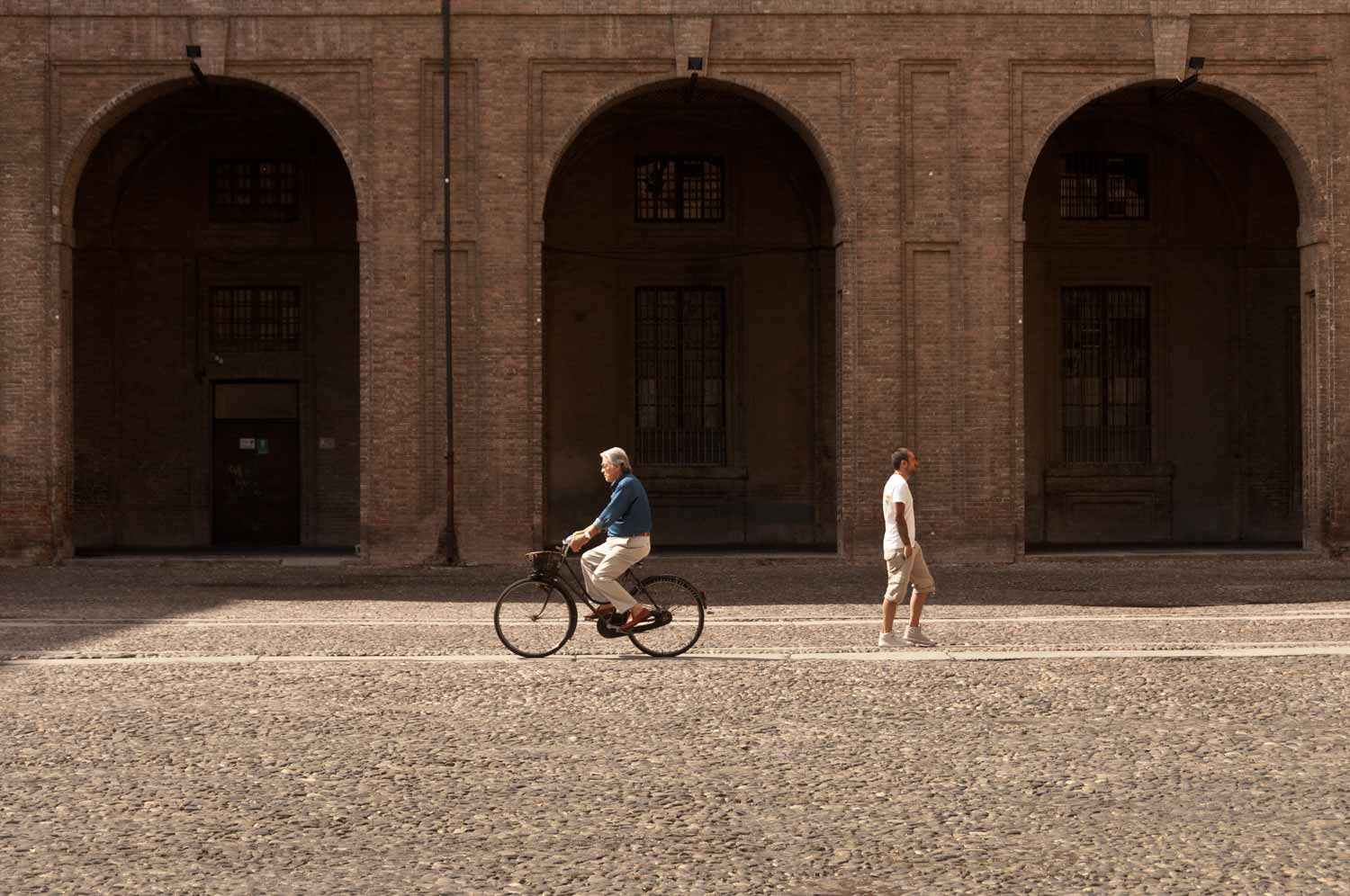 In the internal courtyard, a cyclist passes a pedestrian headed for Parco Ducale.