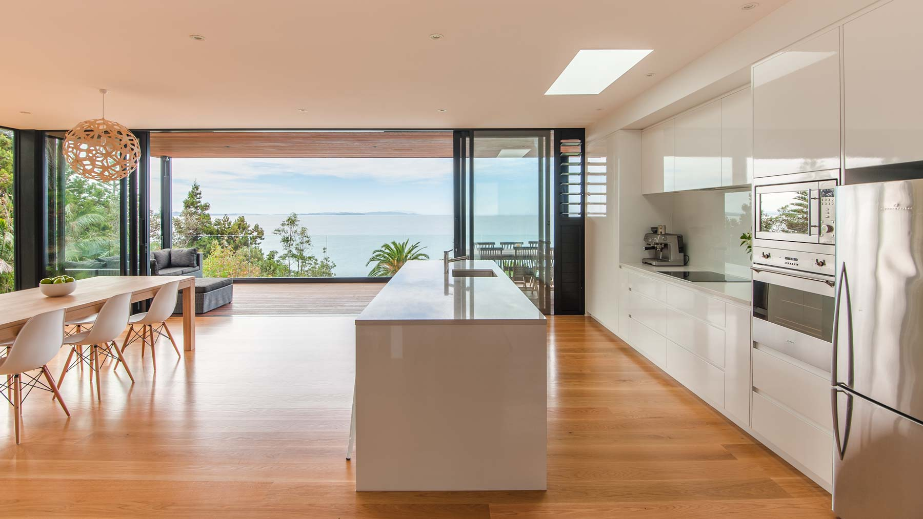 Kitchen, dining, and Great Barrier Island from the main entrance.