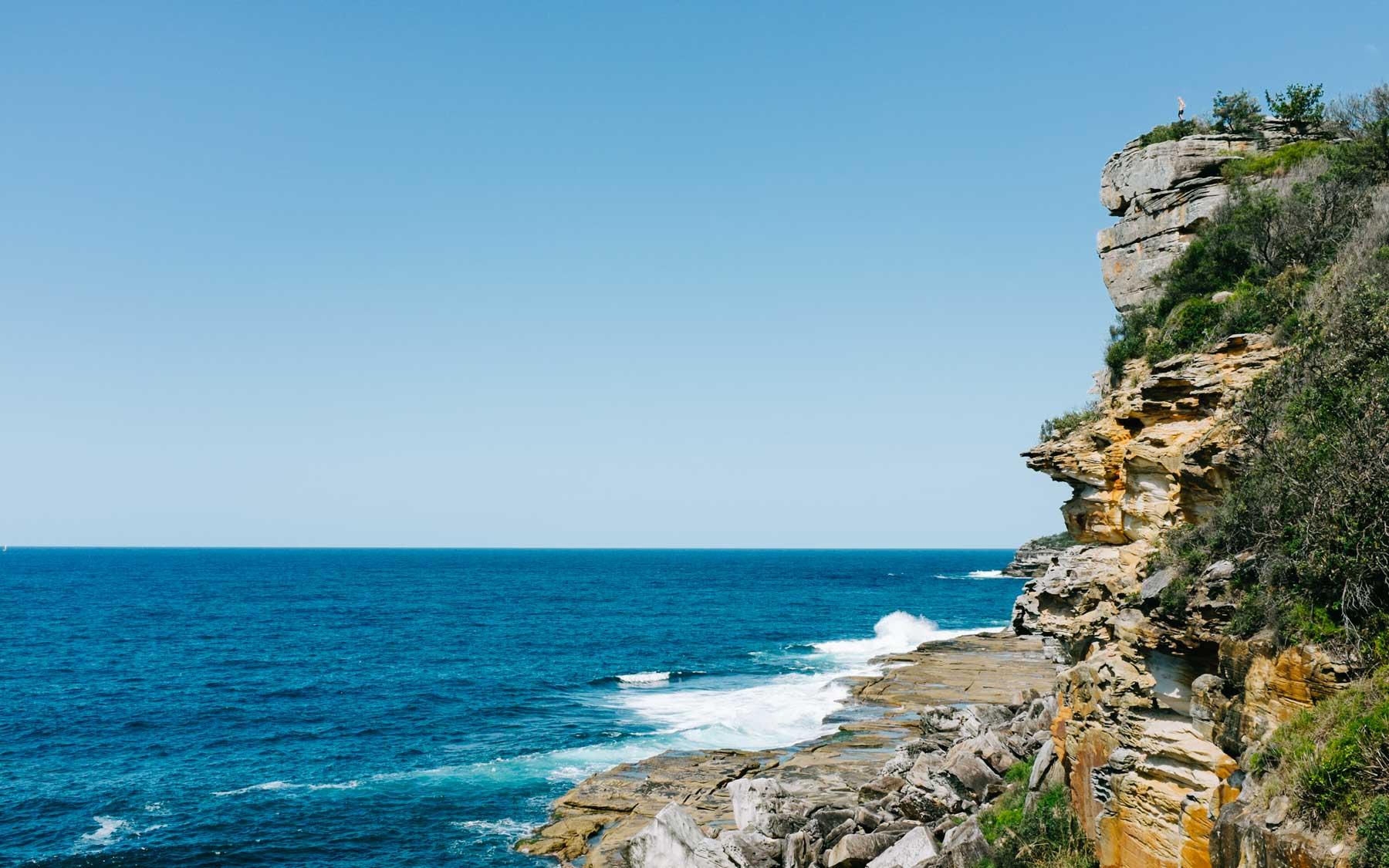 An onlooker stands on a rocky outcrop around from Shelly Beach.